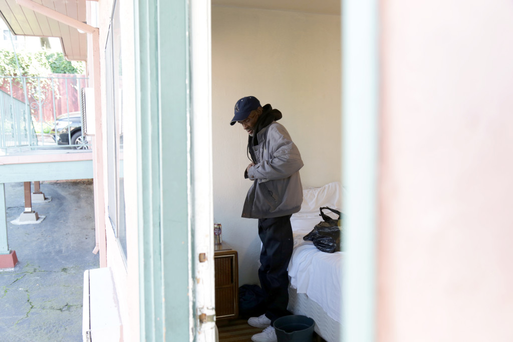 ALISSA AMBROSE/STAT--Foreman prepares to leave his room at an East Oakland motel, where he stayed for one night to escape the cold.