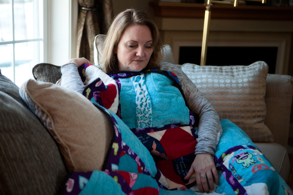 "Portsmouth, NH -- 01/21/16 -- Paula Skelley, mother of Lydia Valdez, poses for a portrait with a ""memory quilt"" made from Lydia's pajamas and bathrobe, in her home on January 21, 2016, in Portsmouth, New Hampshire. (Kayana Szymczak for STAT)"