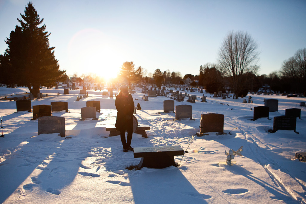 "Portsmouth, NH -- 01/21/16 -- Paula Skelley stands at her daughter Lydia's gravesite bench in the South Cemetery on January 21, 2016, in Portsmouth, New Hampshire. Lydia's gravesite is directly across a small pond from ""Lydia's Garden"", a memorial space dedicated to her which is located on a section of the playground of her former school, the Little Harbour School. Lydia specifically requested to be buried in this cemetery to be close to her school. She was buried right in front of the grave of a young girl, Hannah, who's gravesite inspired the initial end of life conversations that Lydia and her mother eventually had during Lydia's struggle with cancer. (Kayana Szymczak for STAT)"