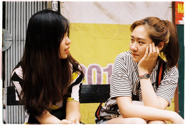 Two women sitting beside each other talking