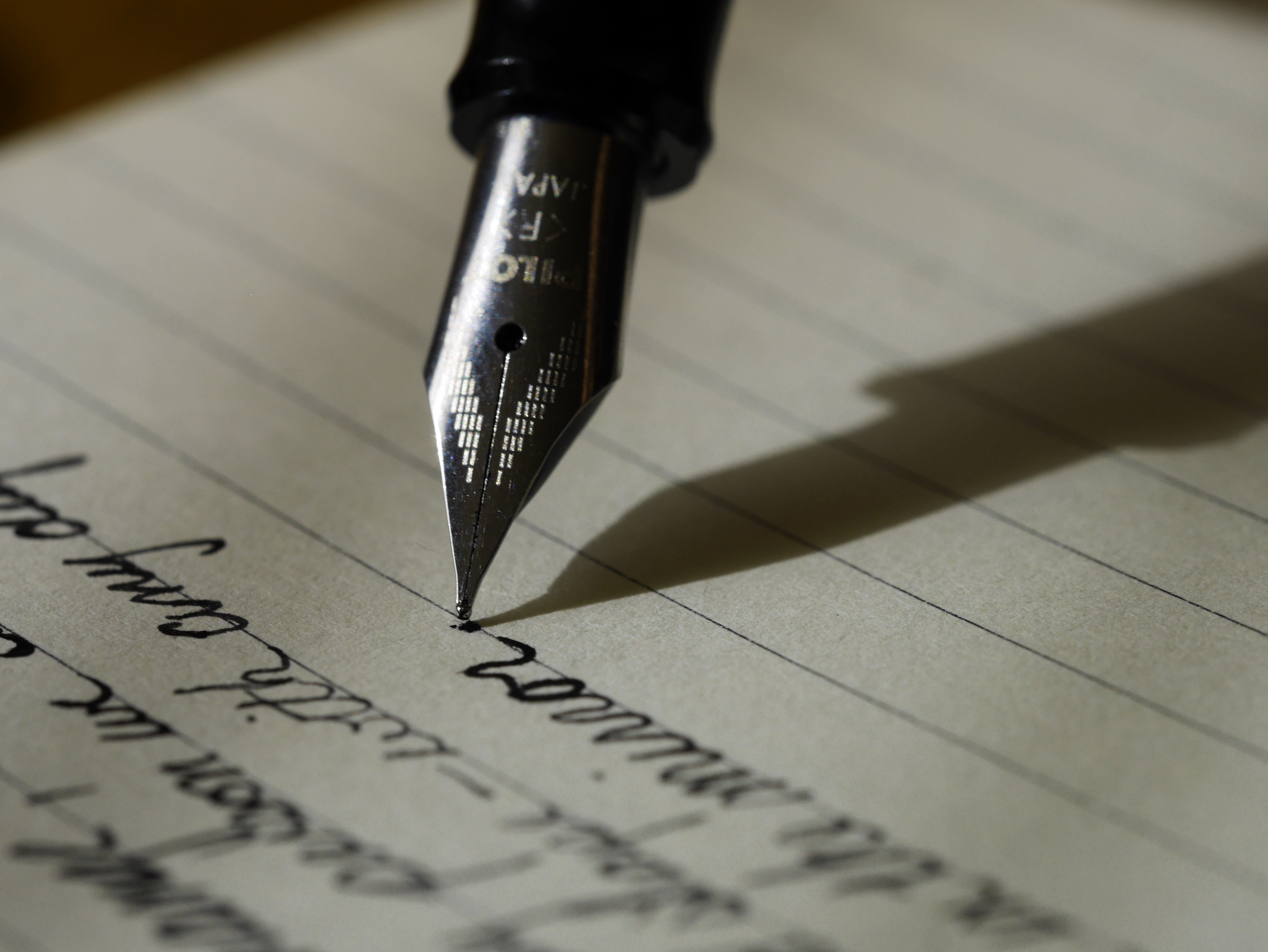 Close-up view of a pen writing on lined paper
