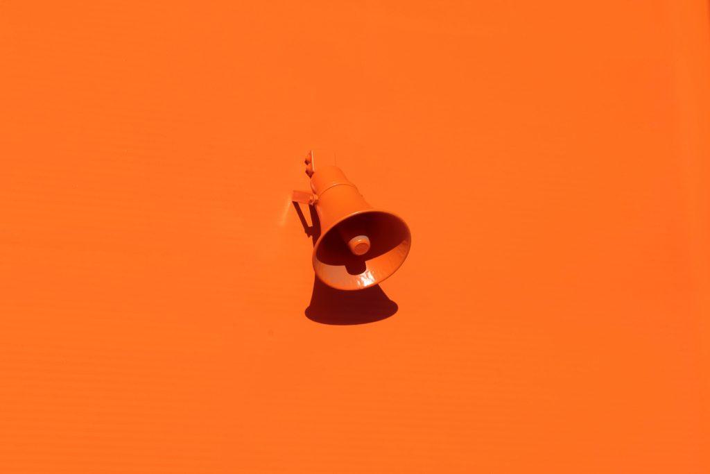 Orange megaphone sitting on orange background