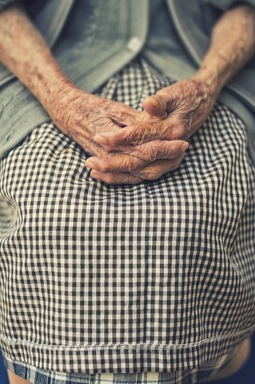 Hands of an older woman folded in her lap